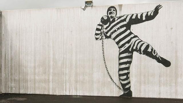 Eine Wand mit einem Graffiti eines Zellinsassen.