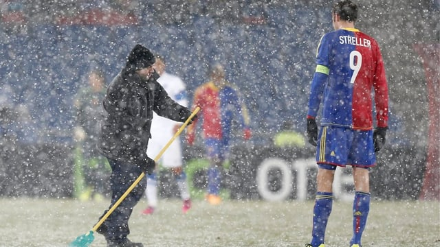 Ein Mann wischt mit einem Besen den Platz, FCB-Spieler Marco Streller schaut zu.