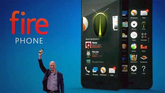 Amazon CEO Jeff Bezos hält ein Smartphone in die Höhe, hinter ihm das Fire-Phone-Logo und ein grosses Bild des Fire Phones.