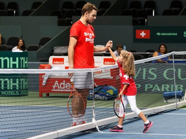 Links auf dem Court steht Stan Wawrinka und rechts steht seine kleine Tochter Alexia. Si halten sich die Hände.