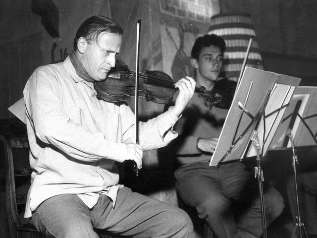 Zwei Männer spielen Geige und sitzen vor ihren Notenständern.