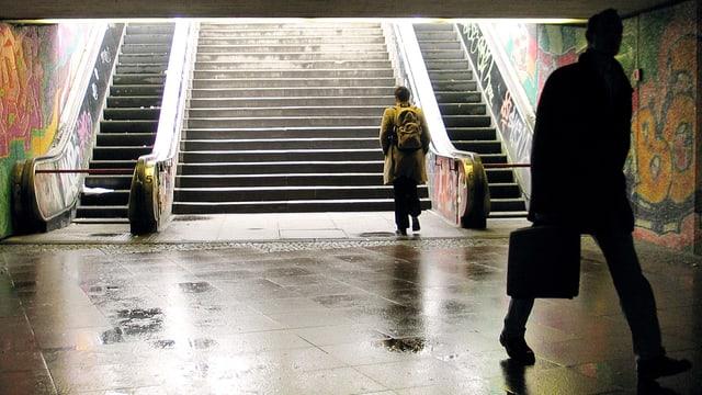 In der Unterfürhrung: Ein Mensch geht Richtung Ausgang und Treppe, ein Mann entfernt sich von ihr.