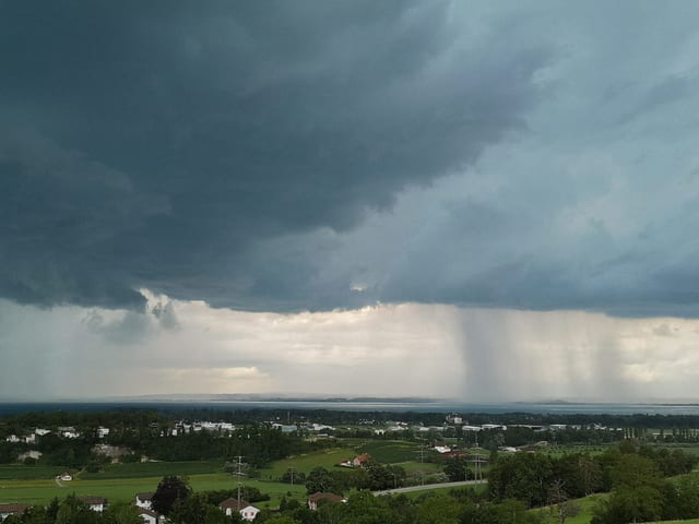 Aus dunkle Gewitterwolken über dem See fällt Regen.