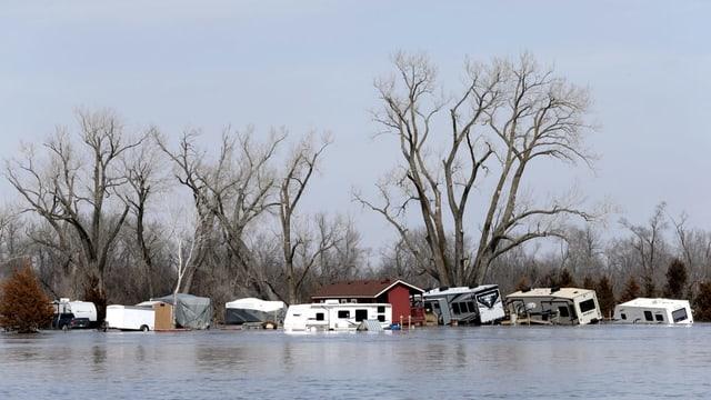 Inundaziuns, chasas e rulottas che nodan en l'aua.