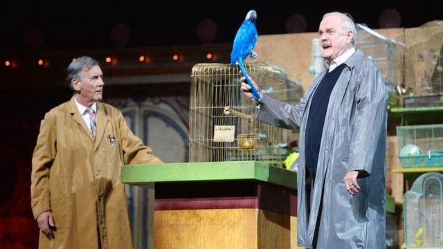 Zwei ältere Herren im Regenmantel. Einer der Herren hält einen blauen Papagei in der Hand.