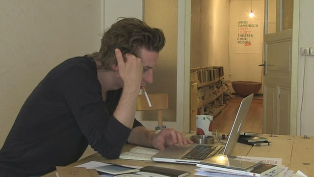 Arno Camenisch cun ina cigaretta en bucca avant il laptop vid scriver.
