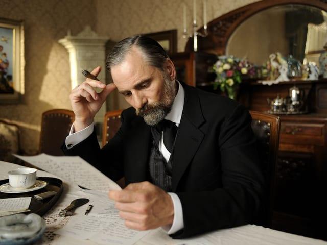 Filmszene: Freud im Anzug mit Zigarre am Tisch, einen Brief lesend.