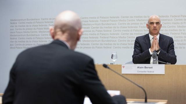 Ein Mann legt die Hände während des Sprechens zusammen.