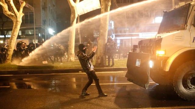 Einzelner Demonstrant vor Wasserwerfer.