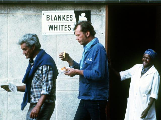 Zwei Weisse verlassen eine öffentliche Toilette mit dem Schild «Blankes/Whites», eine schwarze Toilettenfrau schaut ihnen nach.