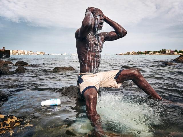 Mann sitzt auf einem Stein im Meer und giesst sich Milch über den Kopf.