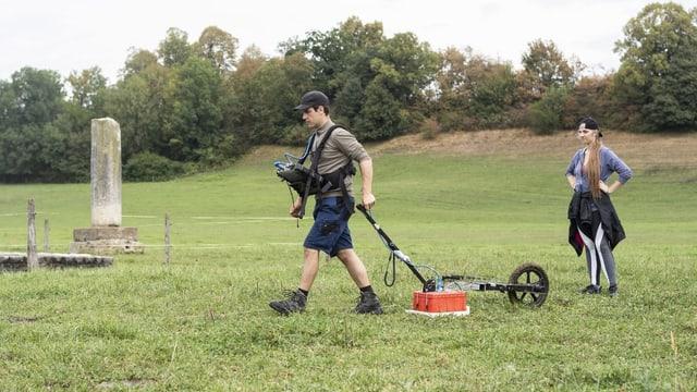 Forscher läuft mit Bildschirm um den Hals und Radargerät an Handwagen über Wiese