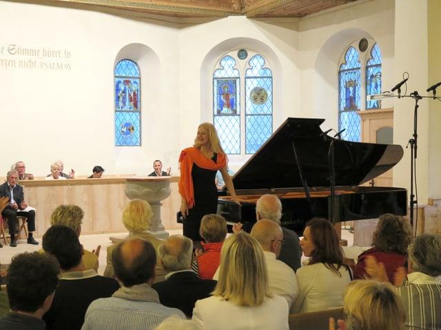Die Pianistin steht vor dem Publikum neben ihrem Flügel.