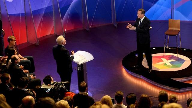 David Cameron sin tribuna e glieud che taidla tiers