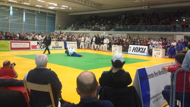 Zwei Judoka kämpfen in der Halle  auf der Matte, während der Schiedsrichter genau hinschaut. Rundherum schauen die Zuschauer gespannt zu