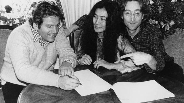 eine schwarz-weiss Aufnahme von John Lennon mit einem Mann, der ein Papier unterschreibt