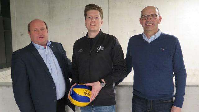 Drei Männer, einer mit Volleyball.