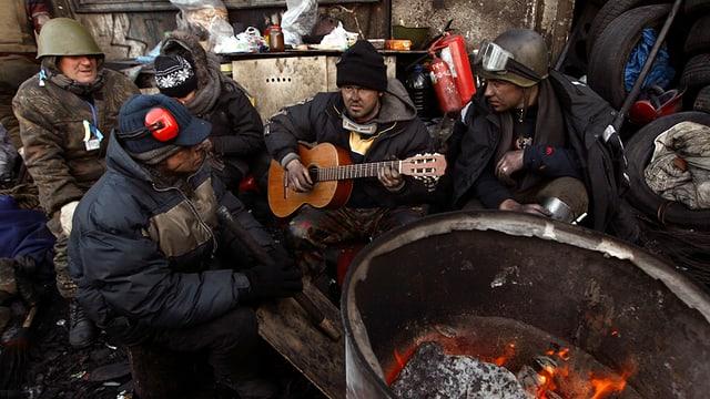 Ukrainische Oppositionelle sitzen am Feuer und singen, einer hält eine Gitarre in der Hand.