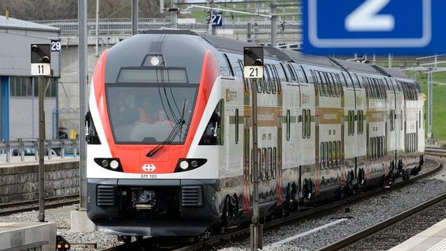 Regionalzug fährt in Bahnhof ein.