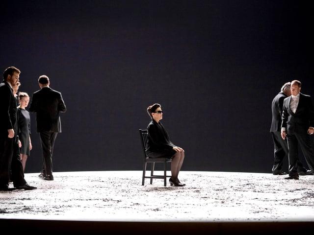 Frau sitzt auf Bühne auf Stuhl und wartet.