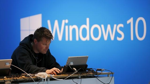 Junger Mann an einem Laptop; im Hintergrund das Logo von Windows 10.