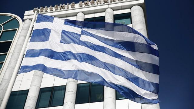 La bandiera greca el vent avant il bajetg da la börsa greca.