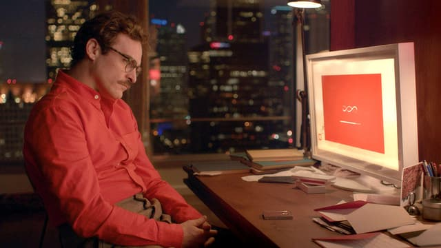 Ein Mann in rotem Hemd sitzt vor einem Computerscreen, der rot aufleuchtet.