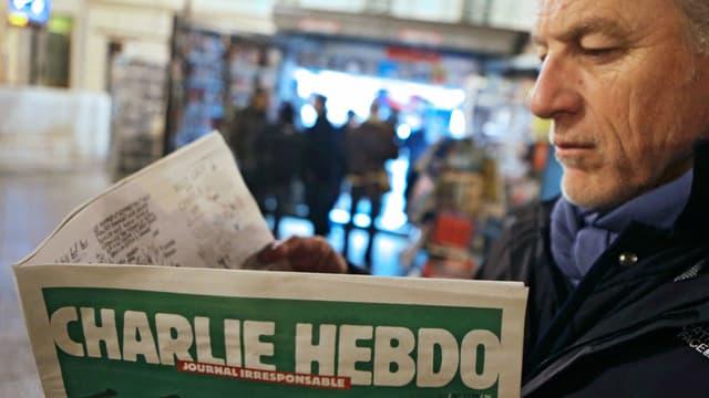 Ein Mann blättert in Charlie Hebdo.