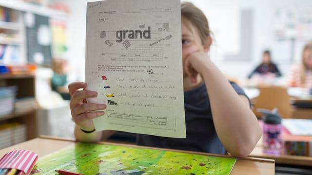 Mädchen sitzt vor Aufgabenblatt mit Französisch-Aufgaben.