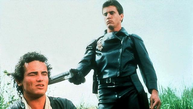 Ein junger Mann in Leder-Outfit hält einem sitzenden Mann eine Pistole an den Kopf.