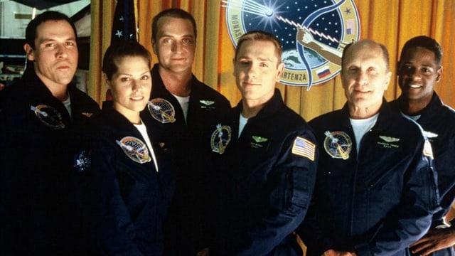 Das Rettungsteam posiert vor dem NASA Logo.