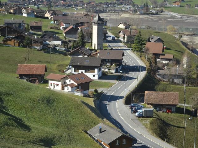 Blick vom erhöhten Zuggeleise über das Dorf mit dem Turm in der MItte.