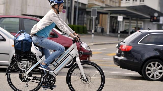 Eine Velofahrerin ist mit einem E-Bike auf einer Zürcher Strasse unterwegs.