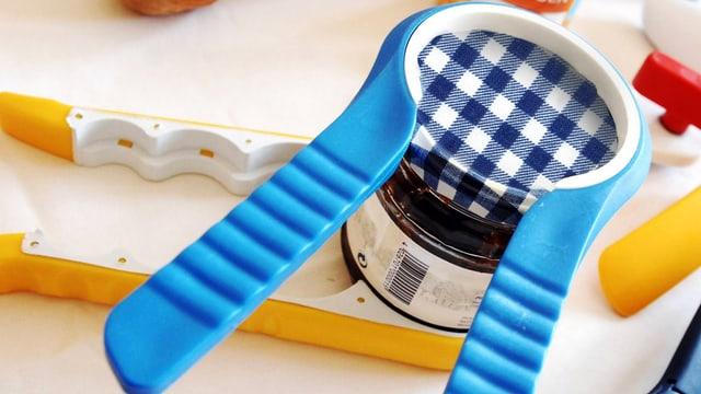 Speziell designter Drehverschlussöffner, der wie eine Zange um den Deckel eines Konfitürenglases sitzt.