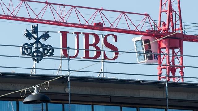UBS-Logo auf einem Gebäude. Dahinter ist ein Kran zu sehen.