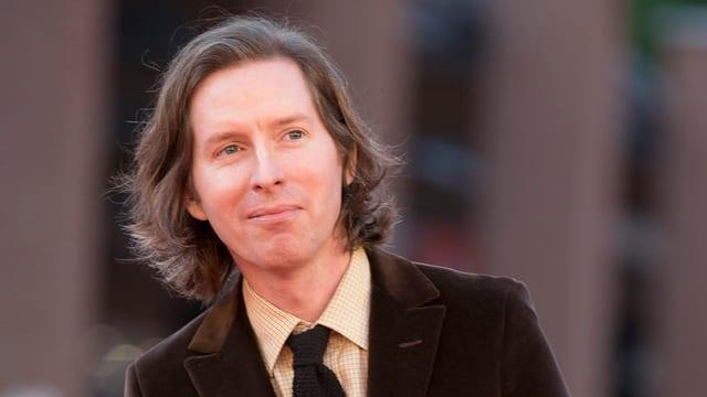 Mann mit langen Haaren in braunem Anzug