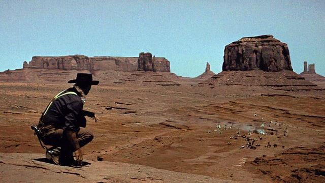 Filmsezene: Ein Mann schaut in einer Wüstenlandschaft auf eine weit entfernte Siedlung mit Zelten.