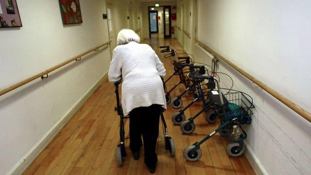 Eine alte Frau mit einem Rollator in einem Pflegeheim.