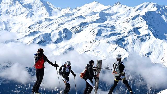 Drei Skifahrer vor Bergkulisse stehend