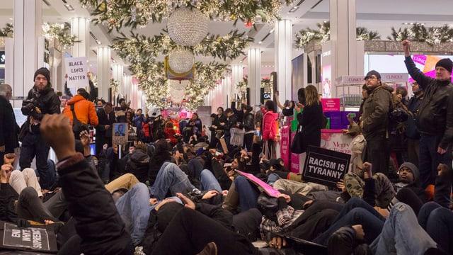 Menschen liegen in einem Kaufhaus auf den Boden