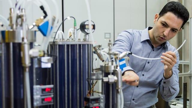 Ein Mann steht vor einer komplizierten Maschine und hält einen Schlauch.