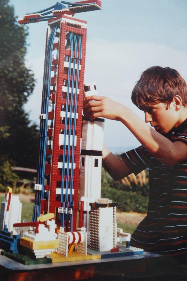 Das Bild zeigt ein altes Foto von einem Jungen mit einer grossen Raktete inklusive Startturm.
