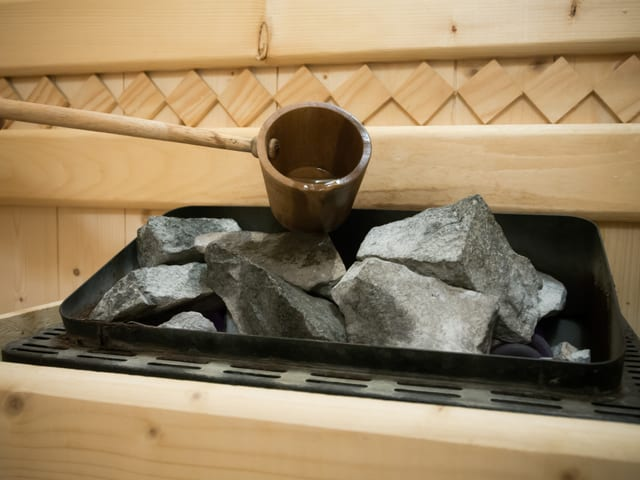 In einer Sauna steht ein kleines Metallbecken mit Steinen. Über diese Steine wird mit einer Holzkelle Wasser geleert.