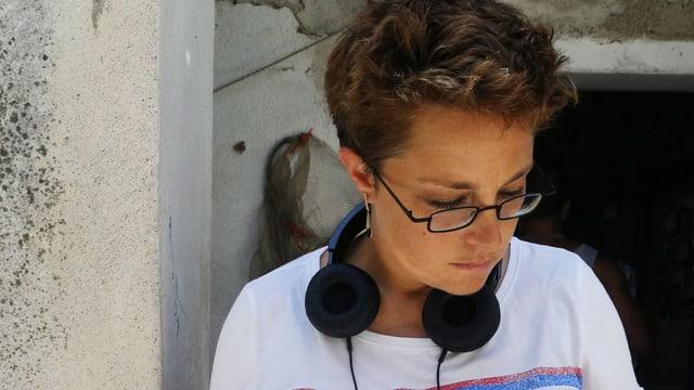 Die Grossaufnahme einer Frau mit Brille und kurzen Haaren. Sie schaut zu Boden. Um den Hals hat sie einen Kopfhörer.