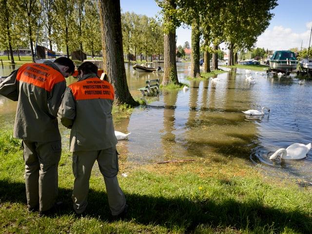 Im Vordergrund zwei Zivilschützer in angeregtem Diskurs. Daneben schwimmen Schwämme im überfluteten Hafenbereich.