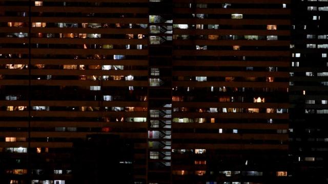 Die Fassade des Torre David bei Nacht mit leuchtenden Zimmern.