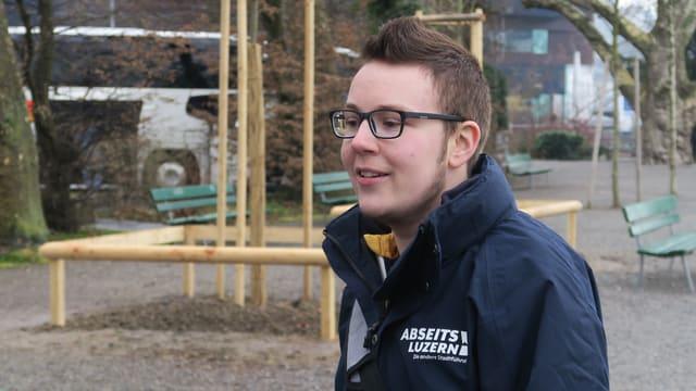 Ein junger Mann mit Brille, kurzen Haaren und einem leichten Bart.