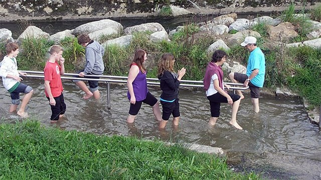 Gruppe marschiert barfuss durchs Wasser