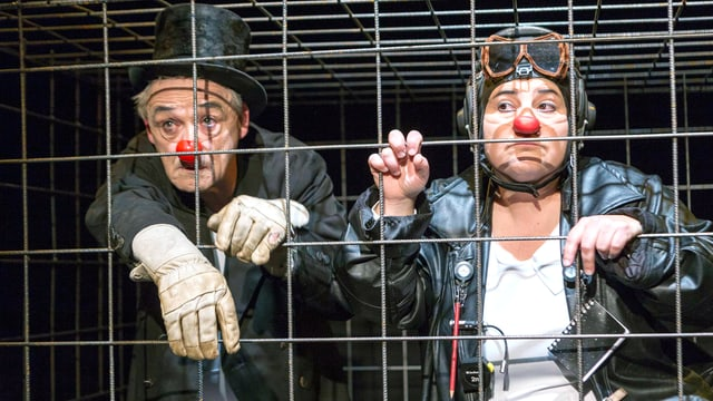 Ein Mann und eine Frau mit Clwonnasen, Zylinder und Fliegerbrille stehen hinter einem Gitter.
