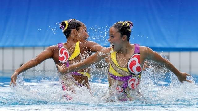 Schwimmerinnen halb aus dem Wasser.